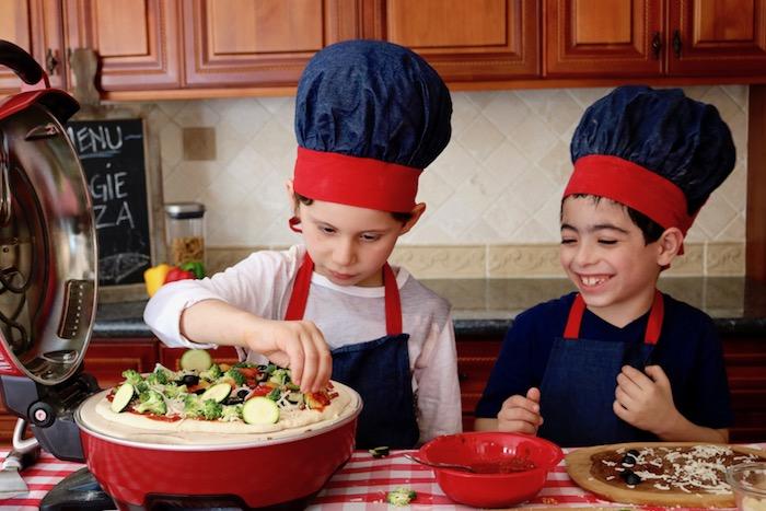 kids making veggie pizza