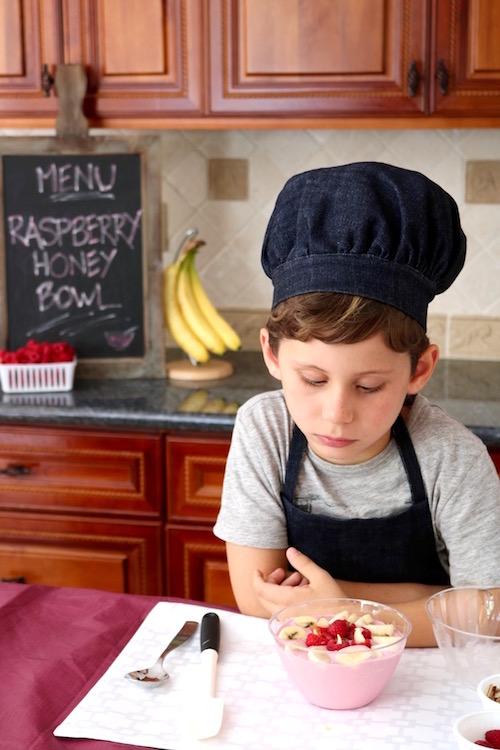 raspberry honey smoothie bowl with boy