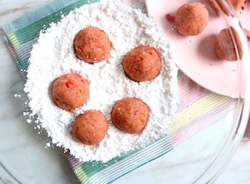 strawberry cake balls in powdered sugar bowl