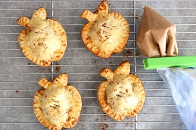 apple hand pies on rack with glaze