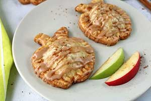 apple shaped hand pies with apples on plate